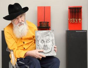 2_Milan Beránek se svým autoportrétem _v pozadí Stroj pro disidenty II a III z konce 70 let_foto Ivan Kahún_repro zdarma